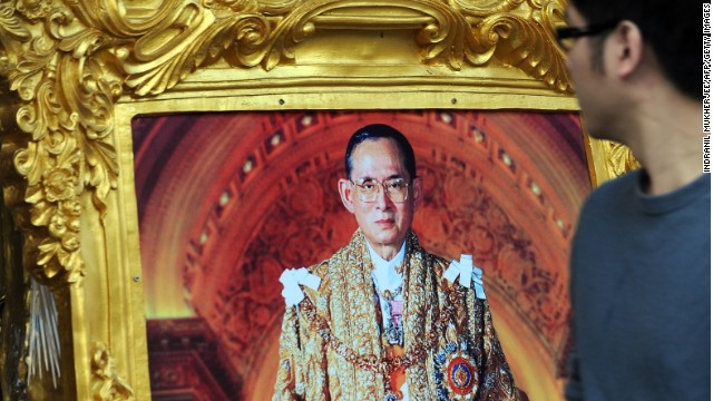 A Thai man walks past a photograph of King Bhumibol Adulyadej in Bangkok on the eve of his birthday on December 4, 2013.