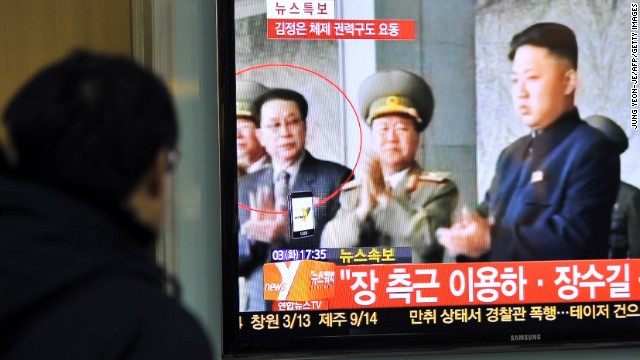 A S. Korean man watches the news about the alleged dismissal of Jang Sung-taek (left), uncle of Kim Jong Un (right).