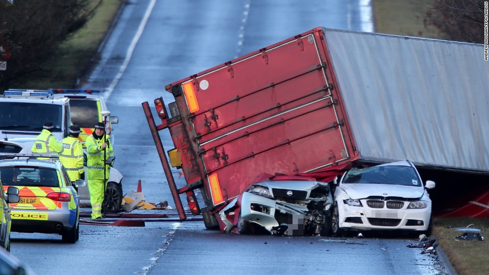 Police work at the scene where a semi-truck was blown onto other vehicles in West Lothian, Scotland, on December 5. The truck driver was killed in the accident.