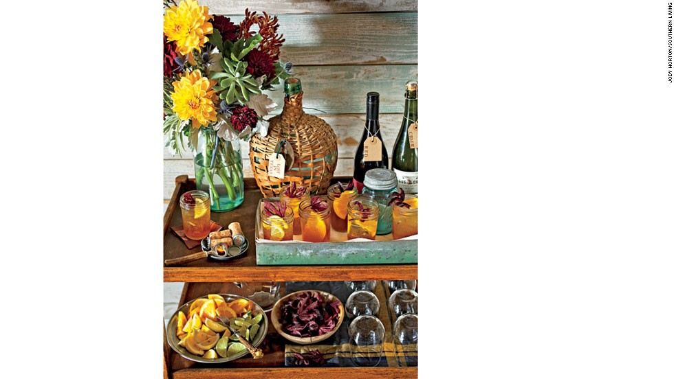 A simple wood bar cart has plenty of room for prepared drinks, garnishes, extra glasses and bottles of wine.