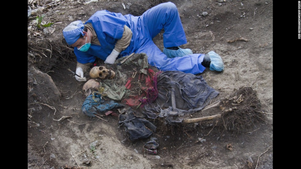 <strong>November 13:</strong> A member of a governmental forensic team unearths the remains of a mother and her teenage daughter from a shallow unmarked grave deep in the Amazonian jungle in southeastern Peru.