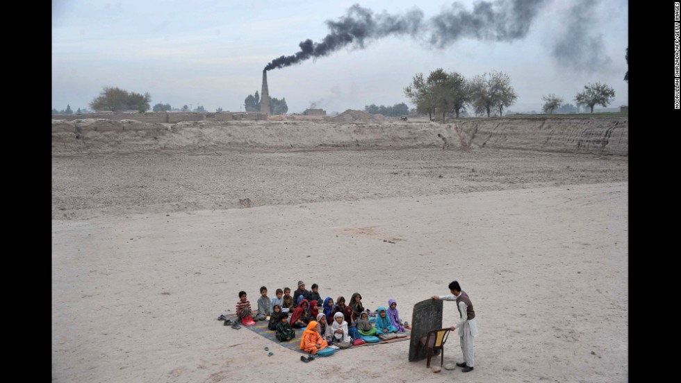 <strong>December 1:</strong> Schoolchildren take lessons at a refugee camp on the outskirts of Jalalabad, Afghanistan.