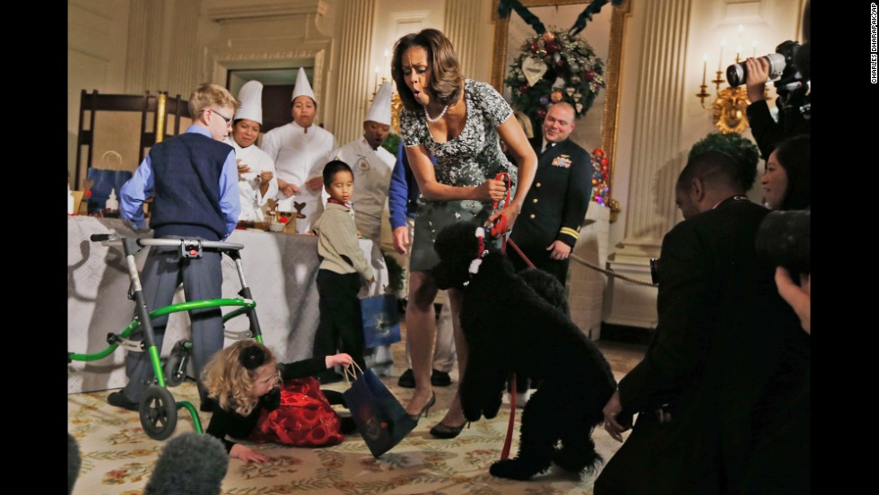 <strong>December 4:</strong> First lady Michelle Obama reacts as 2-year-old Ashtyn Gardner loses her balance after greeting Sunny, one of the Obamas' dogs, during a holiday arts-and-crafts event at the White House.