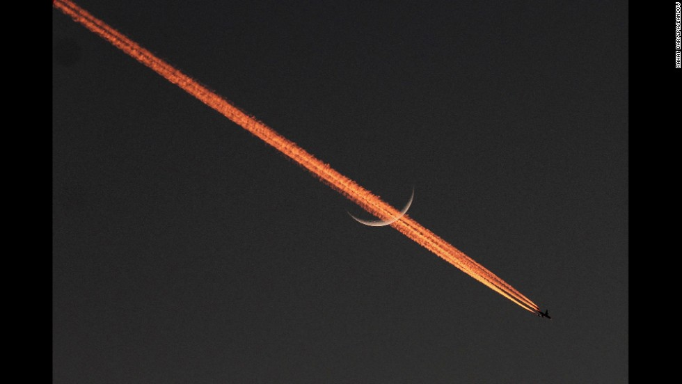 <strong>December 5:</strong> An airplane passes the moon, leaving behind a vapor trail over Lahore, Pakistan.
