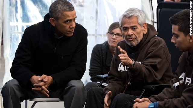 President Barack Obama listens to immigration activist Eliseo Medina during a protest fast on the National Mall in Washington.