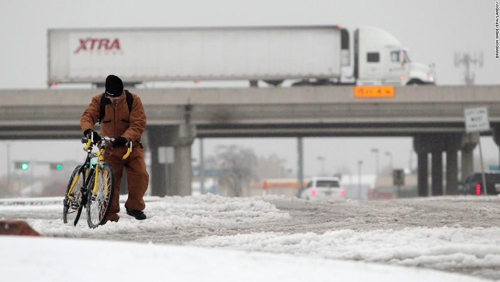Jeff Chupp walks his ice-covered bicycle along Great Southwest Parkway in Grand Prairie on December 6.