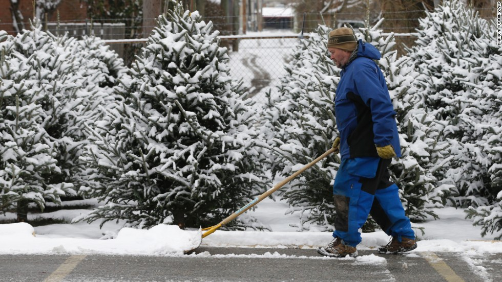 A man clears a path for Christmas tree shoppers in Indianapolis on December 6.