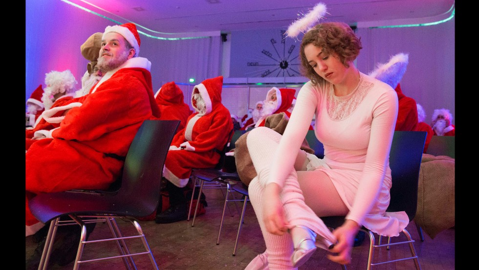 A woman dressed as an angel adjusts her gaiters next to men dressed as Santa Claus during the general meeting of Berlin's Santas and Angels on November 30.