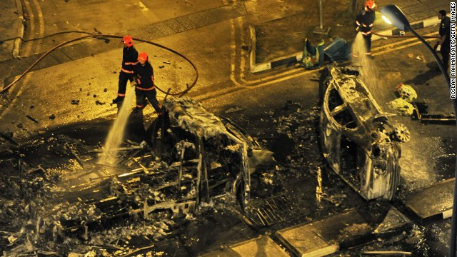 Firemen douse a charred ambulance and a car in the early hours of Monday, after a riot broke out among South Asian workers in Singapore.