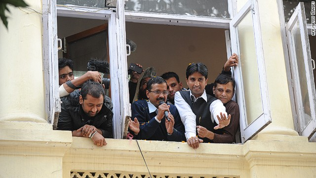 Arvind Kejriwal (center, holding microphone) addresses supporters from his office on December 8, 2013.
