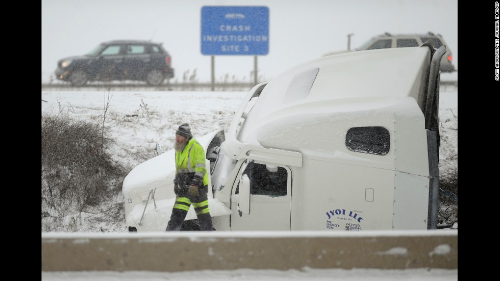 A towing company employee works where a semitrailer jackknifed off Interstate 94 in Racine County, Wisconsin, on December 8.