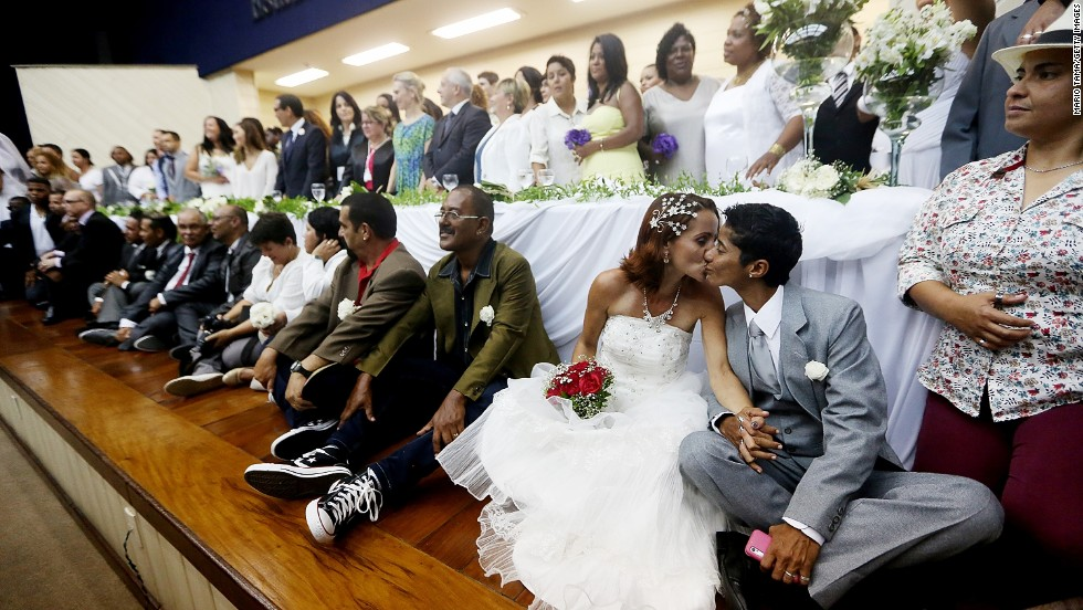 "DECEMBER 9 - RIO DE JANEIRO, BRAZIL: Newly-married couple Emmanuela and Romilda (lower right) kiss at what was billed as the world's largest communal gay wedding. One hundred and thirty couples were married at the event, held at the Court of Justice in downtown Rio. In May,<a href=""http://cnn.com/2013/05/15/world/americas/brazil-same-sex-marriage/""> Brazil became the third country in Latin America to approve same-sex marriage</a> via a court ruling, but a final law is yet to be passed."