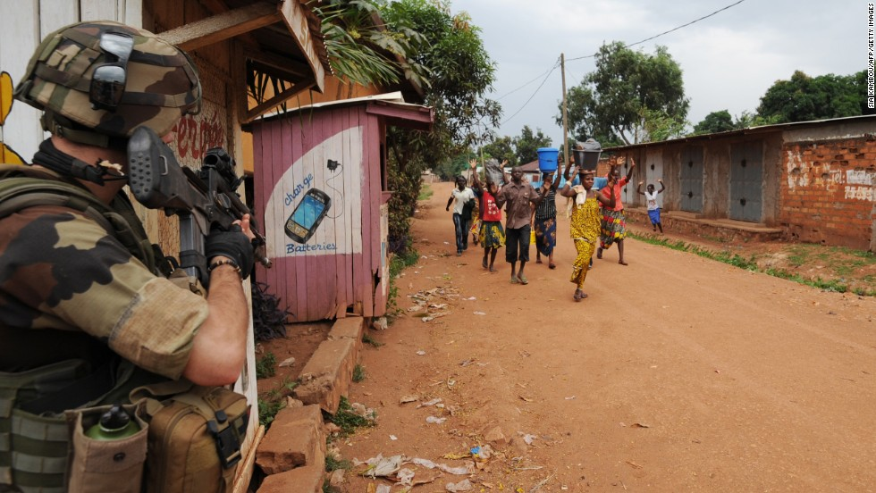 People walk by a French soldier standing guard during a disarmament operation in Bangui on December 9.