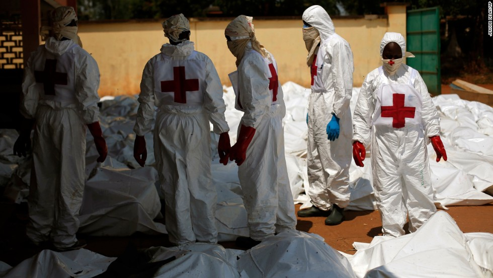 Red Cross employees stand amid dozens of bodies at the morgue in Bangui on December 8.