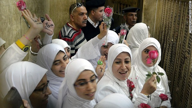 Female members of the Muslim Brotherhood stand in the defendants' cage during their trial in Alexandria on December 7, 2013.