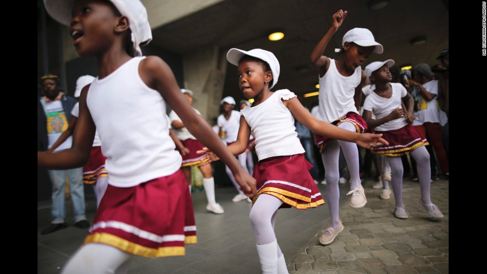 <strong>December 10: </strong>Girls dance during the memorial service for former South African President Nelson Mandela at FNB Stadium in Johannesburg. Thousands of South Africans and more than 90 heads of state gathered to honor the revered leader, who died on December 5. He was 95.
