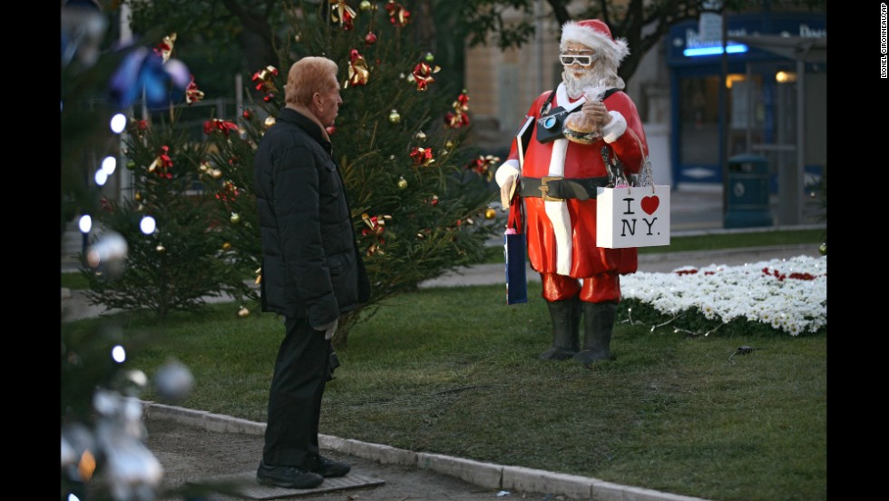 "A man checks out a statue called ""Santa Claus Tourist in the USA"" in Menton, France, on December 9."