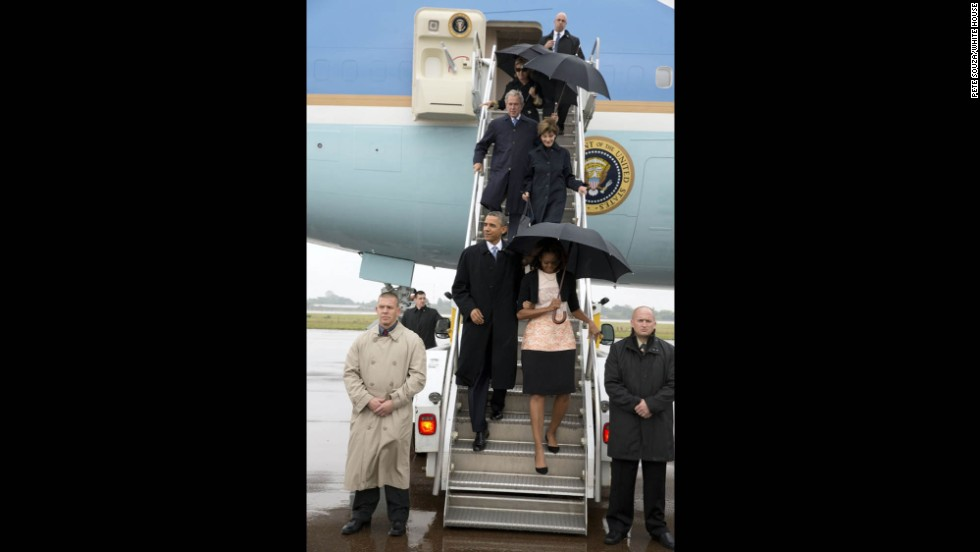 The presidents, first ladies and former Secretary of State Clinton arrive in South Africa.