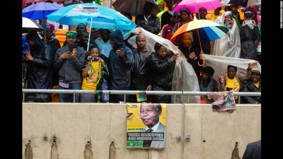 People take shelter from the rain under umbrellas and tarps at FNB Stadium.