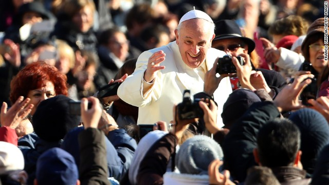Pope Francis waves to the faithful as he arrives in St. Peter's Square for his weekly audience on December 4, 2013 in Vatican City.