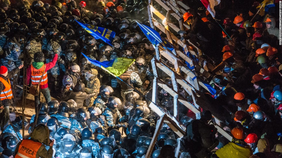 Riot police storm barricades set up by pro-EU protesters in Independence Square on Wednesday, December 11.