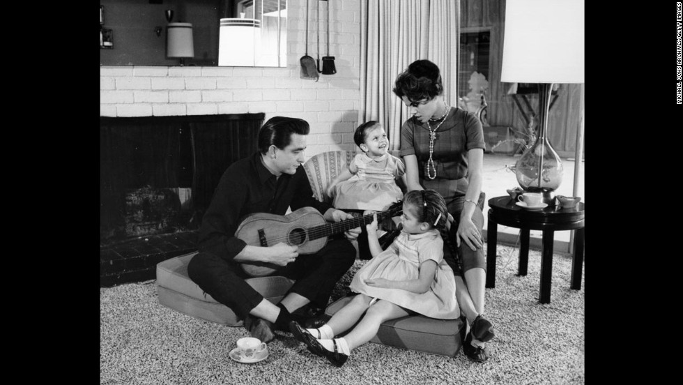 Cash holds a guitar as his then-wife Vivian Liberto and daughters Rosanne and Kathy look on in 1957.