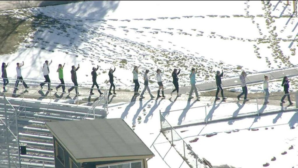 Students walk away from the school in single file with their hands up.