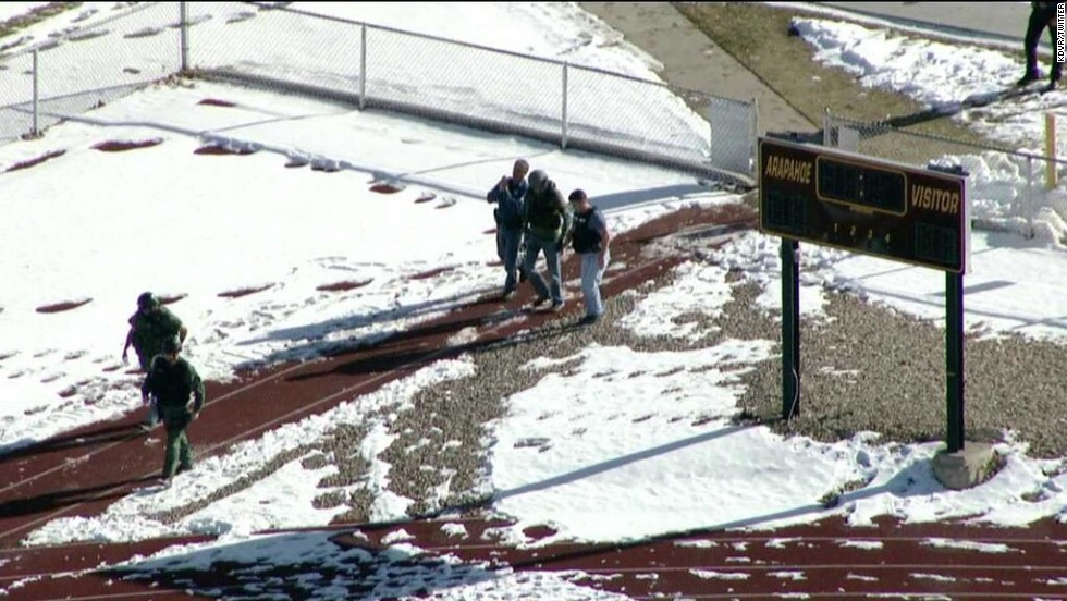 Members of law enforcement are seen outside the school.