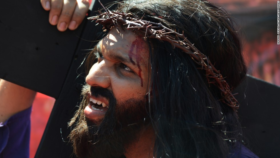 Indian Christian Alan D'Souza portrays Jesus as he carries a cross through a residential area on Good Friday in Mumbai on March 29, 2013. A procession of Indian Christians from all walks of life participated in the march portraying the suffering meted out by Roman soldiers to Jesus on his way to be crucified.