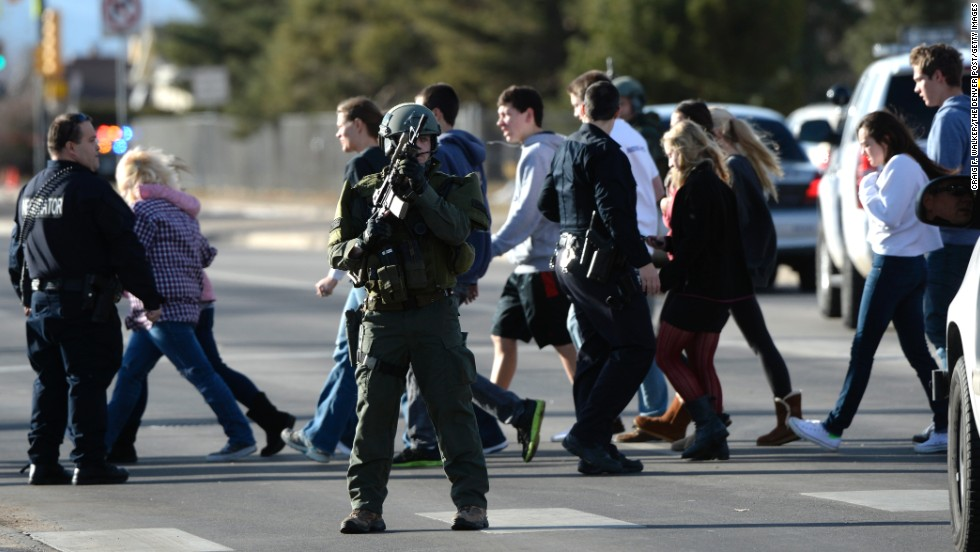 Officers escort students out of Arapahoe High School.