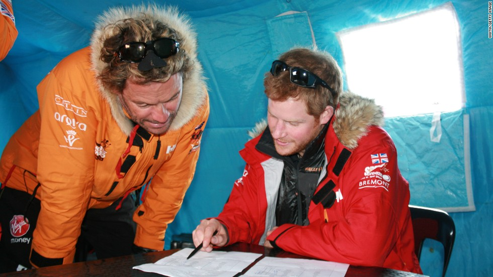 Prince Harry, right, and Dominic West make notes on the weight of each participant and kit during preparations in Novo.