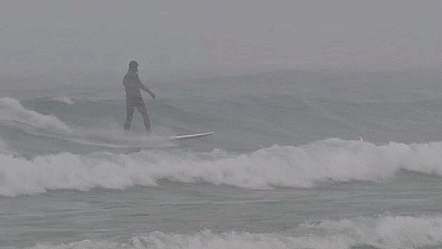 Surfers catch gnarly waves amidst snow