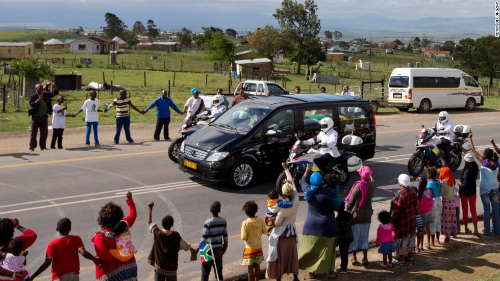 People hold hands as Mandela's hearse proceeds to his hometown and burial site. Mandela became South Africa's first black president in 1994. He had spent 27 years in jail for his activism against apartheid in a racially divided South Africa.