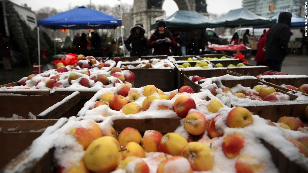 Apples at a Brooklyn street market are covered in snow on Saturday, December 14, in New York.
