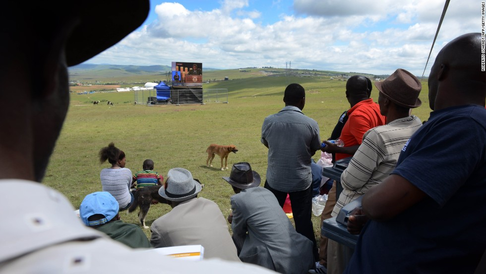 People watch the funeral on a giant screen in Qunu.