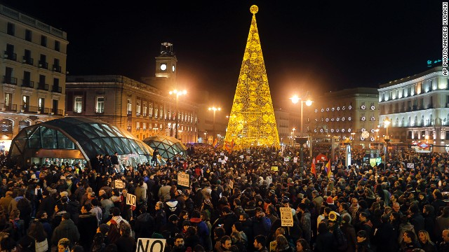 Protestors march through the city center during a demonstration against the government in Madrid on December 14, 2013.
