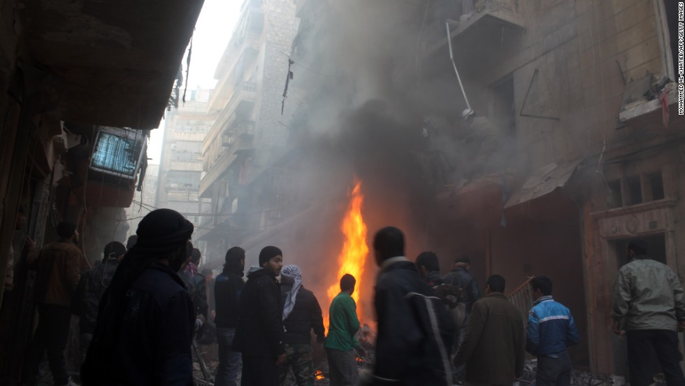 Syrians look at the aftermath of an airstrike on a rebel area of Aleppo on December 15.