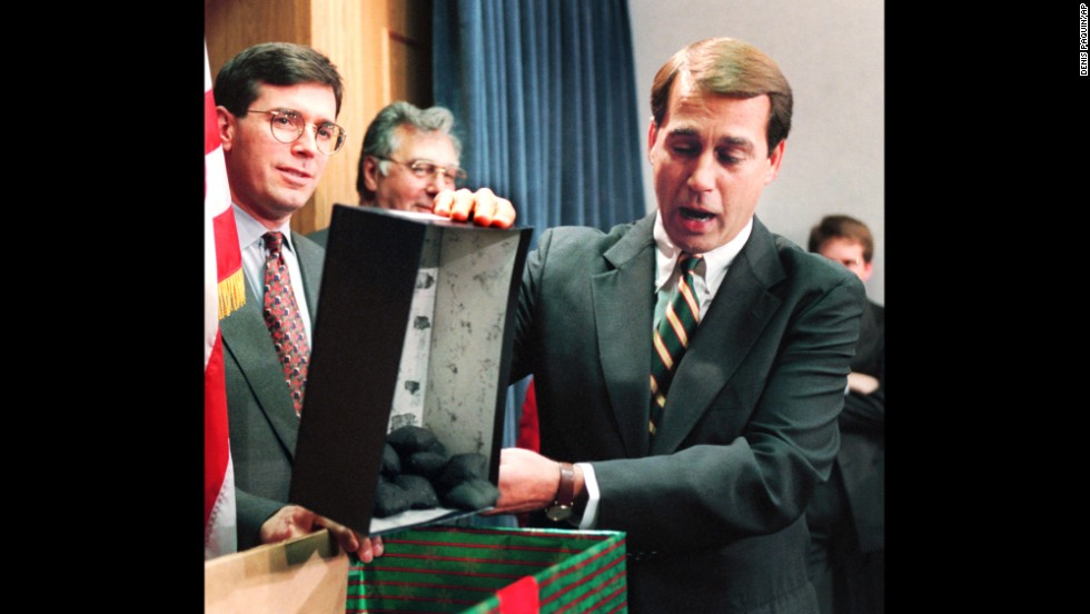 Boehner dumps out coal, which he called a Christmas gift to President Clinton, during a news conference about the federal budget on December 21, 1995. Many government services and agencies were closed at the end of 1995 and beginning of 1996 as a Republican-led Congress battled Clinton over spending levels.