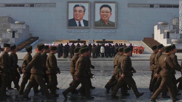 North Koreans soldiers march on Kim Il Sung Square in Pyongyang as others pay their respects beneath portraits of the late leaders Kim Jong Il, right, and Kim Il Sung on Tuesday, Dec. 17, 2013. North Koreans observed the second anniversary of the death of Kim Jong Il. (AP Photo/David Guttenfelder)