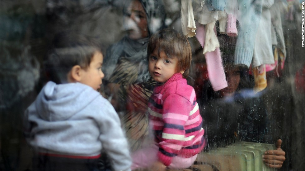 A child looks through a window while food and aid is distributed at a refugee center in Sofia, Bulgaria, on Tuesday, December 17.