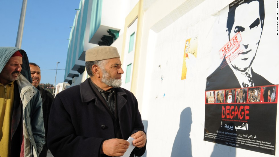 Tunisians look at a movie poster bearing the portrait of deposed President Zine el Abidine Ben Ali.