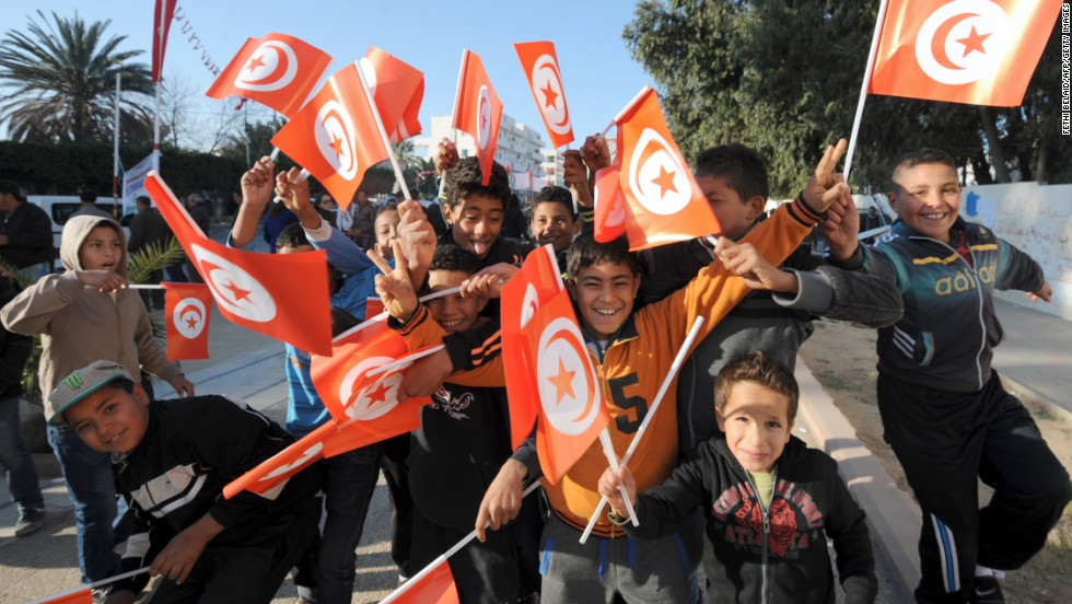 Children wave the national flag in Mohamed Bouazizi square.