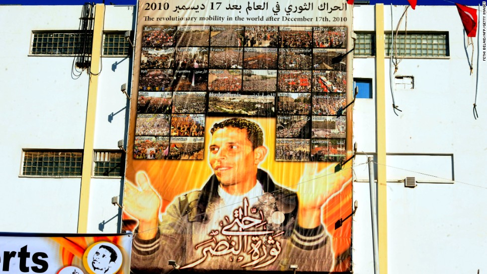 "A giant portrait of Mohamed Bouazizi hangs on the wall in the central town of Sidi Bouzid.<a href=""http://cnn.com/2011/WORLD/africa/01/16/tunisia.fruit.seller.bouazizi/""> The 26-year old fruit seller who struggled with poverty </a>set himself on fire in front of a government building on December 17, 2010 sparking riots across the country. Al Bouazizi died of his injuries on January 4, 2011."