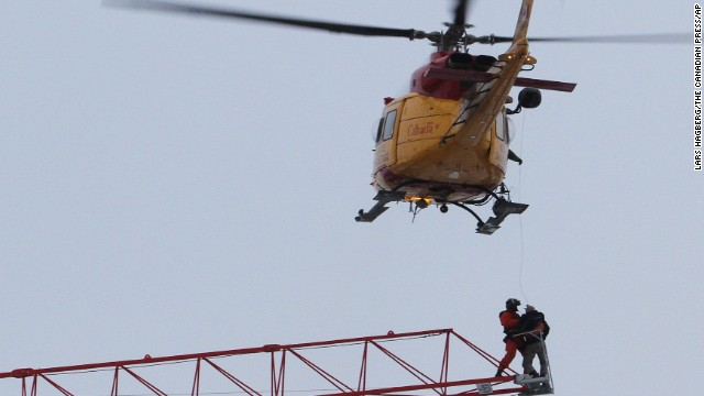 A rescue worker is lowered from a military helicopter to retrieve a crane operator trapped by a raging fire.