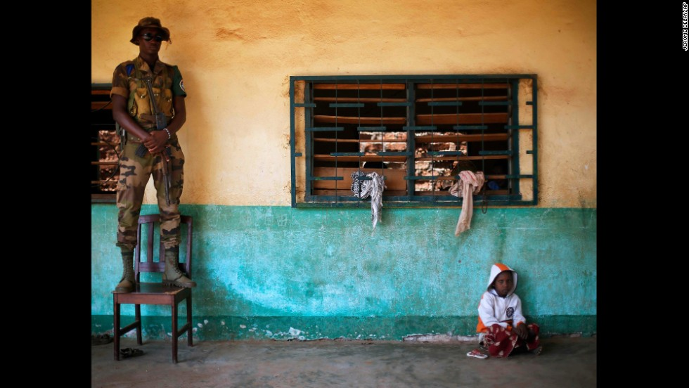 An African Union peacekeeper stands on a chair December 18 as a small child sits on the floor of an Islamic center where refugees have sought protection in Bangui.