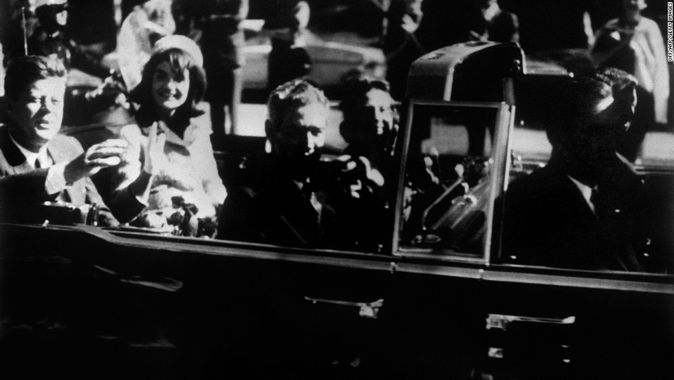 U.S. President John F. Kennedy and his wife, Jackie, ride in an open-top limousine just minutes before Kennedy was assassinated at Dealey Plaza in Dallas on November 22, 1963.