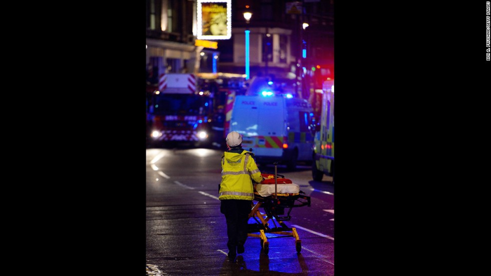 An emergency worker pushes a stretcher along Shaftesbury Avenue.