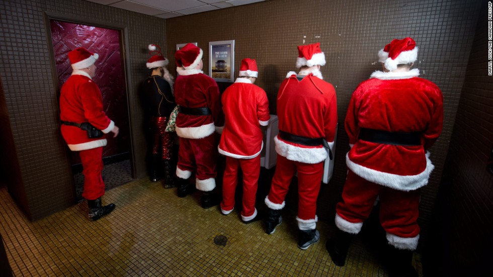 Men dressed as Santa Claus use the bathroom at a bar during a SantaCon event in Vancouver, British Colombia, on December 14.