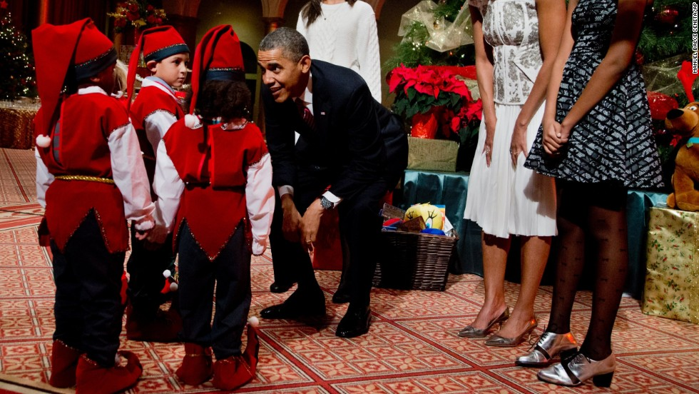 The Obamas greet children dressed like elves at the National Building Museum in Washington on Sunday, December 15.