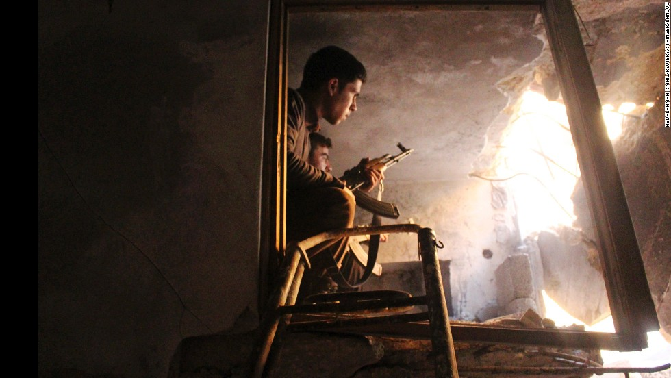 Free Syrian Army fighters sit in a damaged house in Old Aleppo on Saturday, December 21.